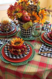 a bright tablescape with a plaid tablecloth, colorful plates and a bold centerpiece of fall blooms, leaves and apples