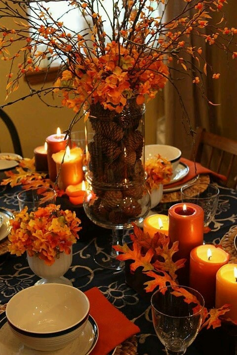 a rust-colored fall table setting with fall leaves and blooms, a floral centerpiece and rust candles
