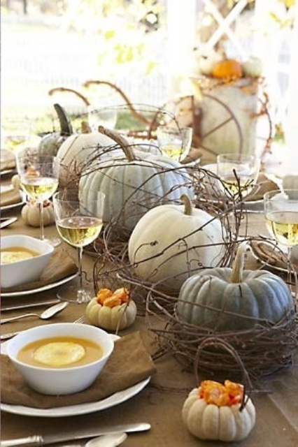 a natural fall tablescape with a brown tablecloth and napkins, neutral pumpkins and vine