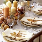 a natural fall tablescape with lots of candles, fall leaves and vine and faux fruits and berries
