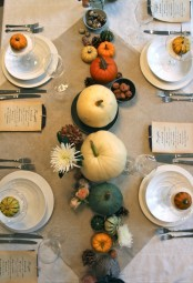 a natural fall tablescape with pumpkins, blooms, pinecones and a neutral tablecloth