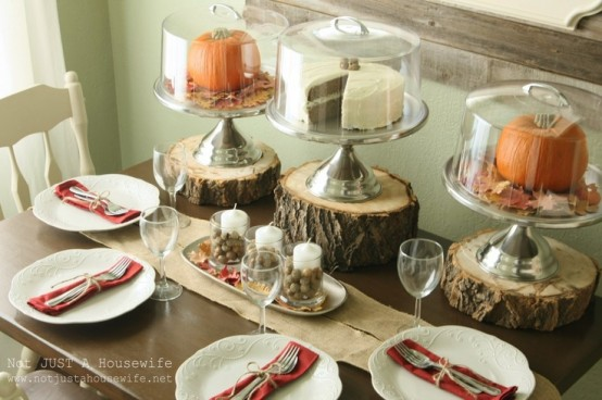 a very simple fall tablescape with a centerpiece of candles and nuts, tree stumps with cloches and pumpkins in them
