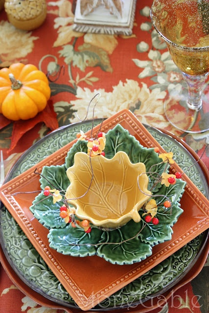 a colorful fall tablescape with whimsy and bright plates including fall leaf ones plus faux pumpkins