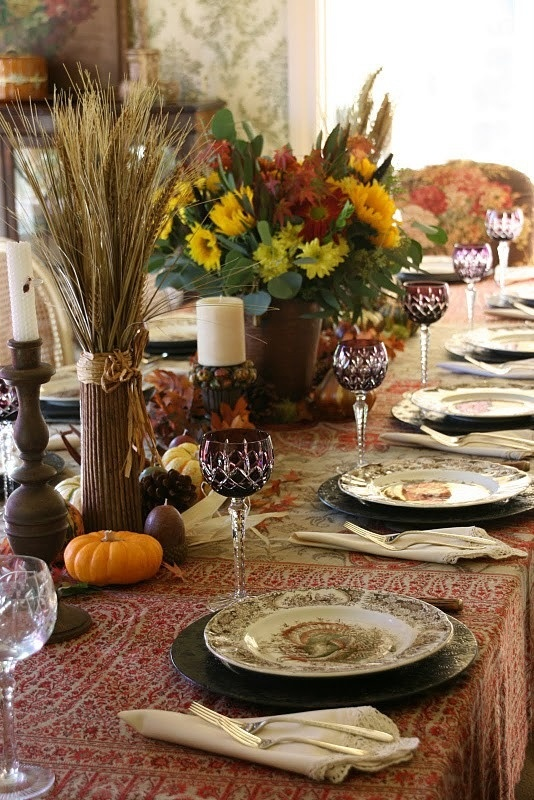 a vintage-inspired tablescape with a printed tablecloth, faux pumpkins, pinecones, wheat and floral arrangements and printed plates