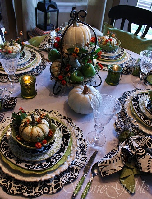 a black and white tablescape spruced up with green touches, with faux pumpkins, berries and leaves
