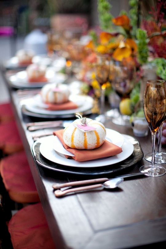 a fall tablescape with dark chargers, glasses, bright napkins and faux pumpkins for each place setting