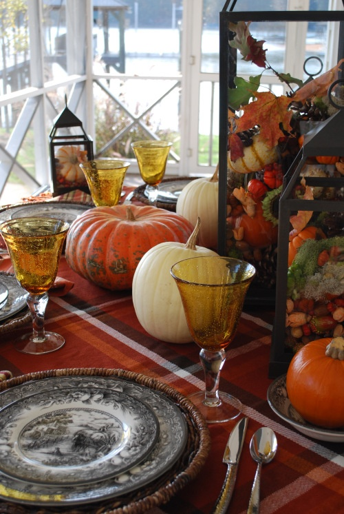 a bold traditional fall tablescape with printed textiles, plates, woven placemats and lanterns filled with nuts and acorns plus natural pumpkins