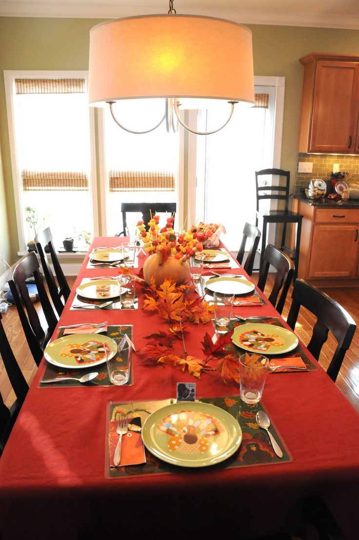 a colorful fall tablescape with bright textiles, fall leaves and a pumpkin that holds skewers with fruits and veggies
