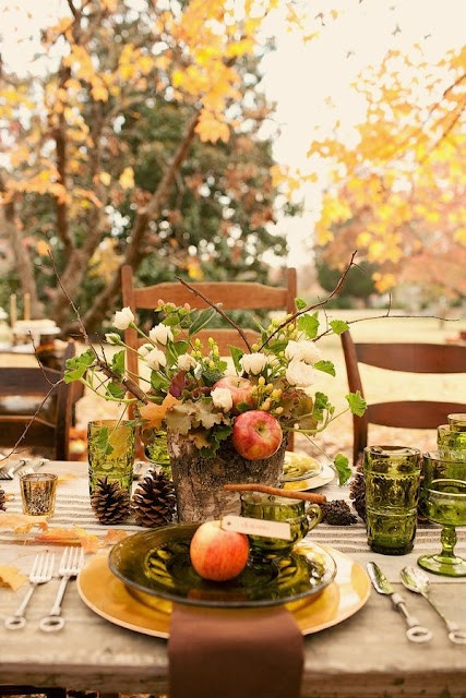 a fall tablescape with a stump centerpiece with blooms, cotton and apples, green glasses and plates, gold chargers and cinnamon sticks