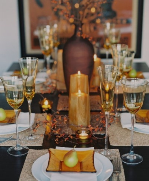 a fall tablescape with amber glass plates, amber candles, berries, and glasses plus pears for each place setting