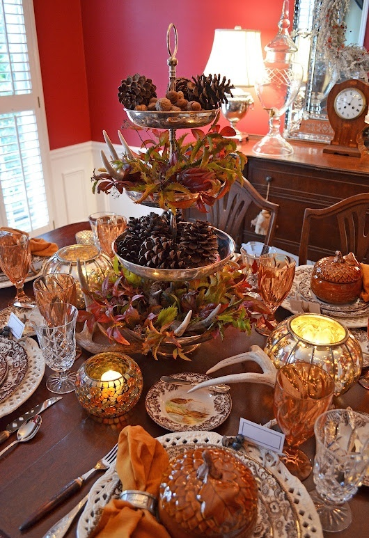 a bold traditional fall table with antlers, fall leaves, pinecones, colorful glasses and mercury glass candleholders