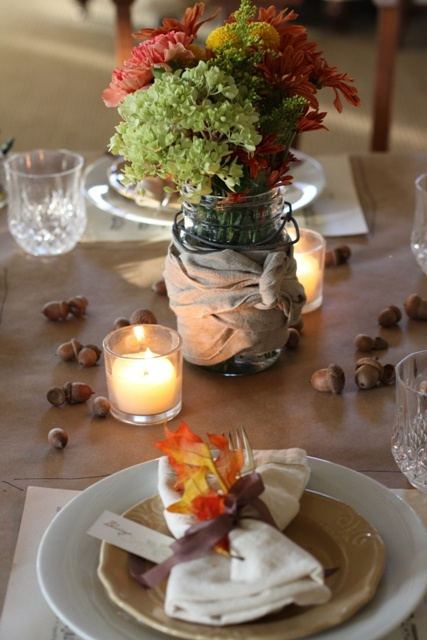 a natural fall table setting with a bright floral arrangement, nuts, candles, a napkin with a fall leaf and ribbons