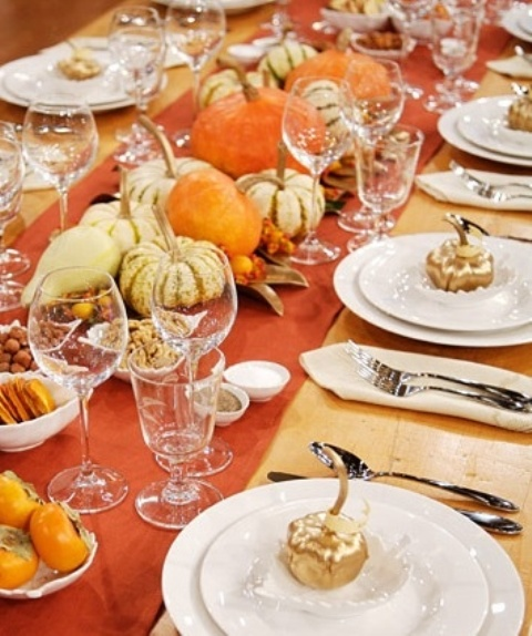 a colorful fall tablescape with an orange table runner, real pumpkins and veggies for decor and not only