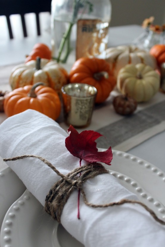 faux pumpkins for a centerpiece and a napkin wrapped with twine and fall leaves make the tablescape bold and fall-like