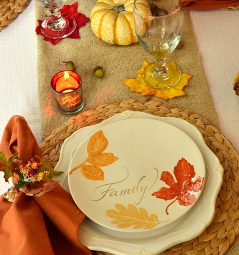 a fall tablescape with a burlap runner, woven placemats, bright napkins and plates with printed leaves