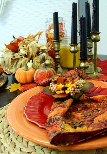 a bright tablescape with printed plates, woven placemats, fabric pumpkin and corn husks centerpiece and tall black candles
