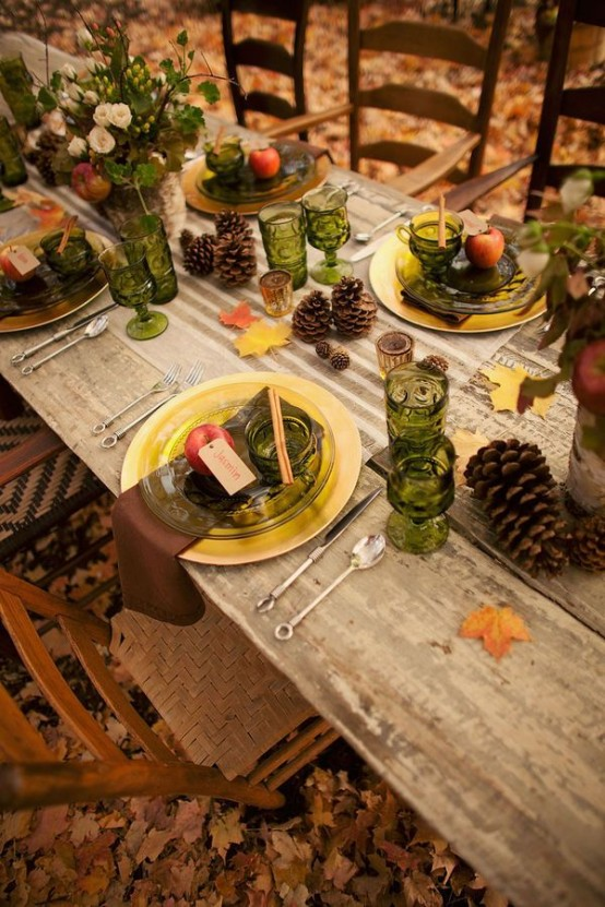 a fall tablescape with pinecones, fall leaves, apples, green glasses and florals plus gold chargers