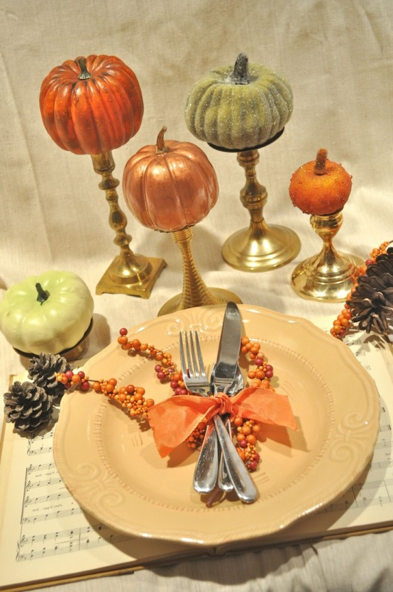 a simple fall place setting with faux pumpkins, a plate on a music note placemat, pinecones and berries