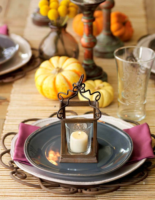 a colorful fall table setting with a purple napkin, a candle mini lantern, faux pumpkins and a woven table runner
