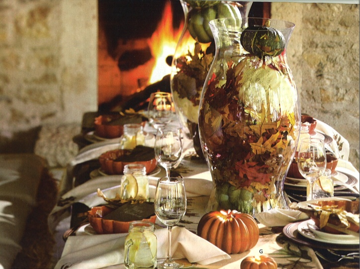 a vintage inspired tablescape with pumpkin plates, faux pumpkins, fall leaves and large glass jars with fall leaves
