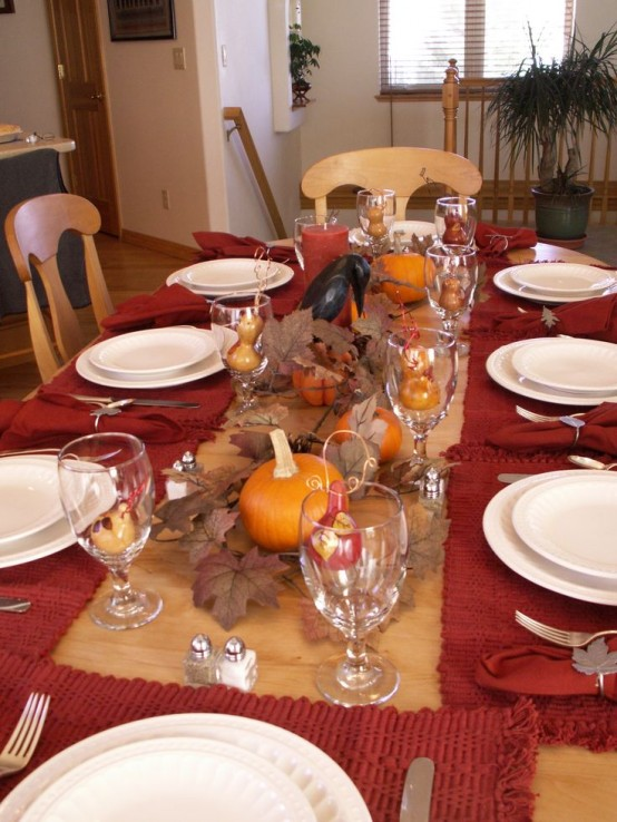 a bright fall tablescape with red textiles, fall leaves, pumpkins and a blackbird will do for a Halloween party, too