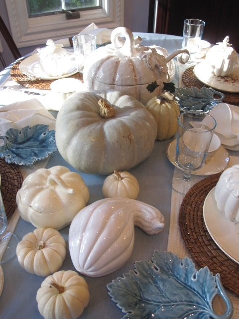 a blue and white tablescape with natural and faux pumpkins, a blue table runner and leaf plates plus woven placemats