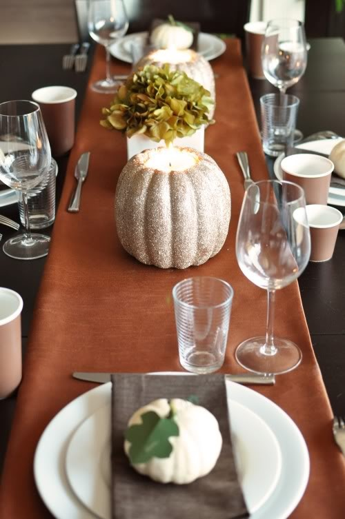 a bold fall tablescape with a rust table runner, white pumpkins with leaves and green hydrangeas