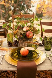a lush fall tablescape with green glasses and plates, with pinecones, gold chargers, cinnamon sticks and apples looks very natural