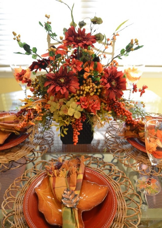a rust, orange and green tablescape with a lush floral centerpiece with berries and woven placemats and colorful plates