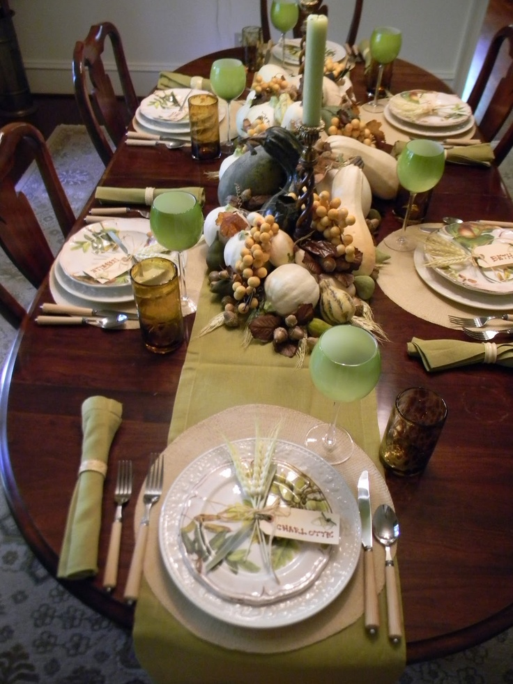 a cozy fall tablescape in neutrals and green, with green glasses and candles, natural pumpkins, nuts and acorns