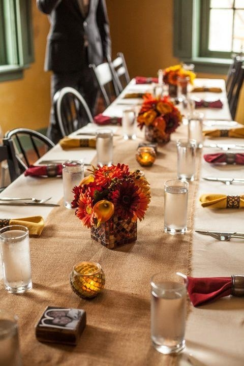 a fall tablescape spruced up with bold napkins, bold blooms and candles in candleholders