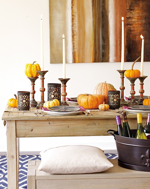 a fall table setting with tall candles, natural pumpkins, elegant candleholders and a bamboo table runner