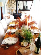 a bold fall tablescape with a rust-colored tablecloth, natural pumpkins and greenery, tall candles