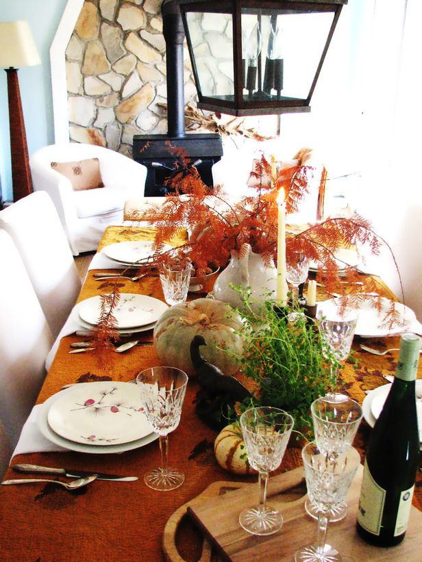a bold fall tablescape with a rust colored tablecloth, natural pumpkins and greenery, tall candles