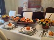 a simple fall tablescape with silver chargers and napkins, a wooden bowl with faux pumpkins and gourds and some blooms