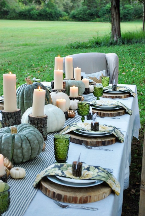 a natural fall tablescape with a striped table runner, heirloom pumpkins and candles on tree stumps