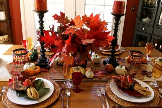a bold deep red and rust tablescape with an arrangement of fall leaves, candles, napkins, faux pumpkins and gourds plus woven placemats