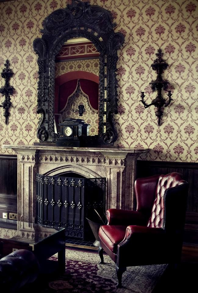 a refined Gothic living room with neutral printed wallpaper, refined dark furniture, a sophisticated mirror and a fireplace with a metal screen