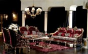 a sophisticated Gothic living room with black curtains, burgundy velvet furniture, a gold coffee table and a chandelier