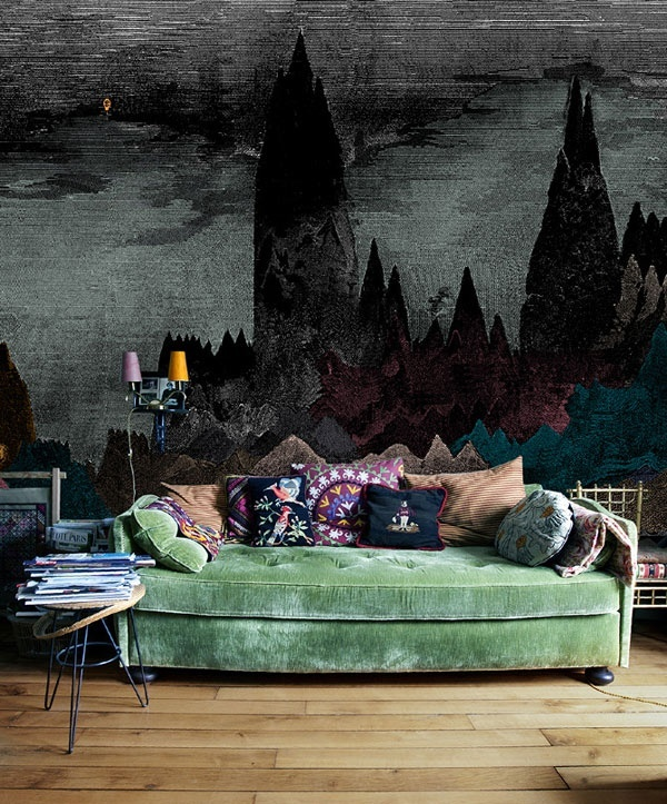 a Gothic living room with a touch of bright color   a green sofa with colorful pillows and a statement moody wall mural