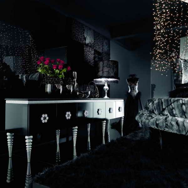 an all dark modern Gothic living room with black walls, refined furniture, a light canopy and bold artworks