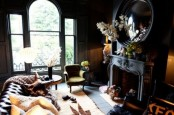 a chic Gothic living room with black walls, a catchy shaped window, a black fireplace and a round mirror, a green chair and a leather sofa