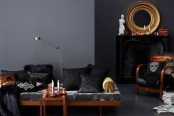 a modern Gothic living room with grey walls, a black statement wall with a fireplace, candles, a mirror in a gold frame, a sofa and bold and black pillows