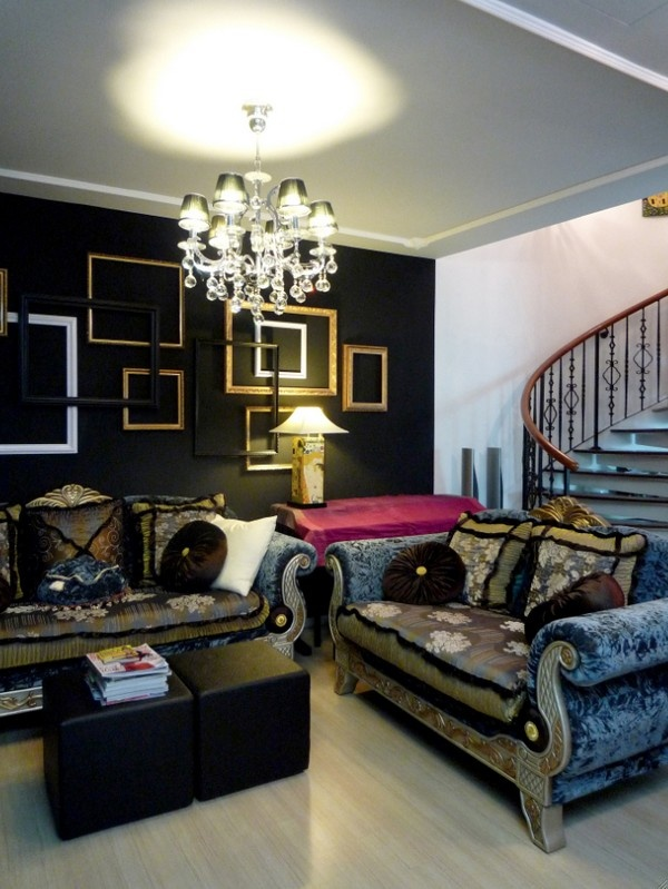 a refined soft Gothic living room with a black wall with empty frames, exquisite vintage furniture, a crystal chandelier and black ottomans