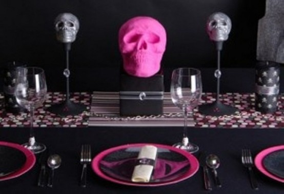 a modern glam pink and black Halloween tablescape with a printed runner, skulls, pink plates and black linens is a fun and bold idea