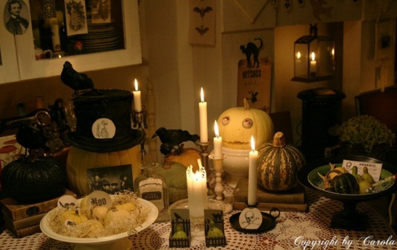 a chic neutral Halloween table setting with scary pumpkins, candles, crows and faux veggies looks mysterious and not too scary