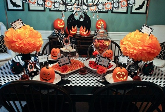 a bold black, white and orange Halloween tablescape with paper pumpkins, black linens and goblets, jack-o-lanterns and lots of sweets