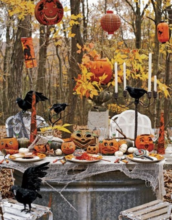 an outdoor Halloween tablescape with jack-o-lanterns, fall leaves, candles, elegant porcealin, crows and cheesecloth