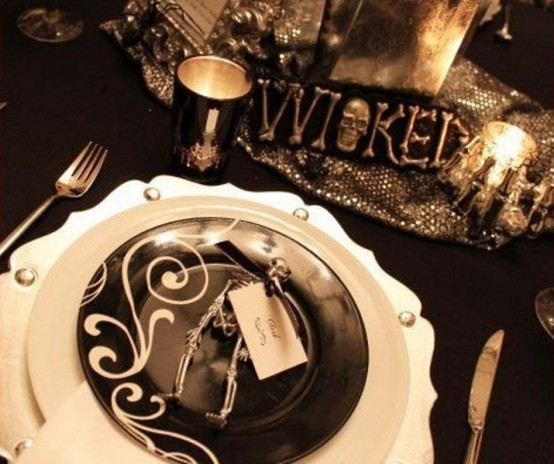 a stylish black and white Halloween party table with contrasting plates, candles, silver candleholders and a runner and a sign is very cool