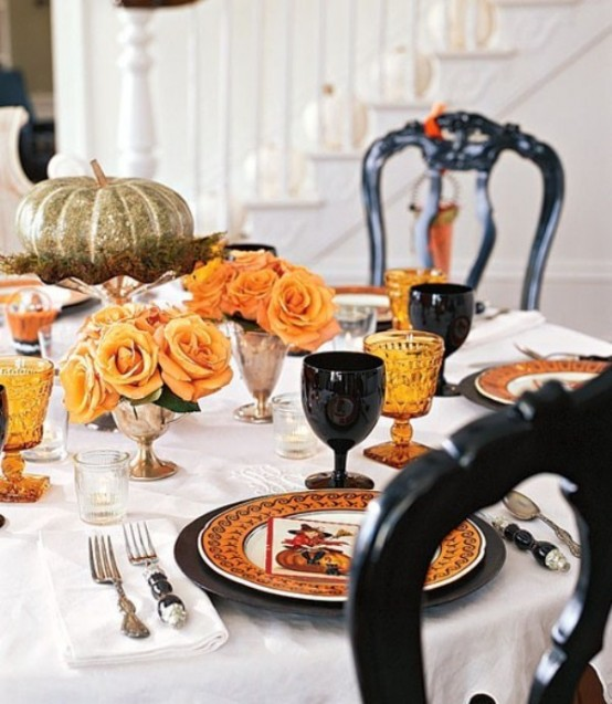 an elegant Halloween tablescape with orange and black plates and glasses, orange roses in gold vases and a metallic pumpkin on a stand